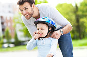 Father helping daughter with bike helmet