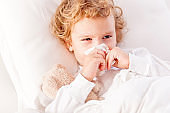 Little boy in bed blowing nose
