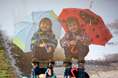 Reflection of two little boys, squat on puddle with umbrellas
