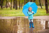Little boy standing in a puddle