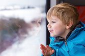 Beautiful toddler boy looking out train window outside and trave