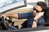 handsome man talking on the phone in a convertible car