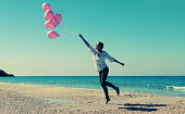 Young woman  walking on the beach with pink balloons