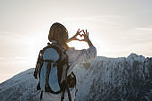 Woman at top of mountain making heart shape with hands