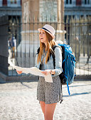 happy attractive exchange student girl visiting Madrid city reading map