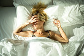 Young woman awaked by sunlight coming in hotel room