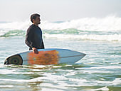 Surfer standing in the sea with surfboard.
