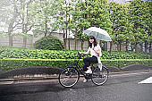 Young Japanese Woman Riding Bicycle on Rainy Day in Tokyo