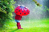 Cute little girl with umbrella playing in the rain