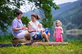 Adorable young family with kids hiking at a lake