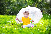 Little girl with colorful umbrella playing in the rain