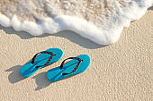 Turquoise Sandals On The Beach Near Water's Edge