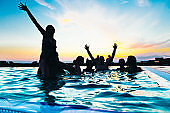 Friends enjoying a sunset pool party