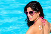 Woman sunbathing and enjoying summer with sunscreen