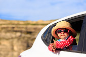 cute little girl travel by car in mountains