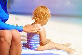 parent applying sunblock cream on child shoulder