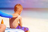 parent applying sunblock cream on son shoulder