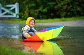 Cute boy with colorful rainbow umbrella on rainy day