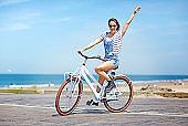 happy young woman riding bike near North sea