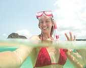 Cheerful woman snorkelling taking selfie