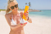 Woman with sunscreen bottle on the beach