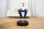 Man Holding Remote Control Of Robotic Vacuum Cleaner