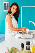 Woman smiling while washing a cup  in blue kitchen