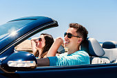 Young man driving with girlfriend in convertible