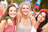 Girl friends with arms around each other at music festival