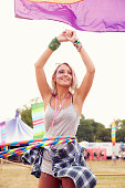 Blonde woman dancing with hula hoop at music festival, vertical
