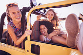 Mixed racial group of friends laughing on summer road trip