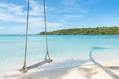 Swing hang from coconut palm tree over beach sea