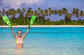Woman holding snorkeling fins standing in blue water