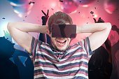 Young happy man has party with virtual reality glasses.