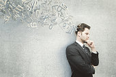 Thinking businessman on concrete background