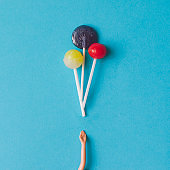 Doll hand with lollipops. Minimal concept. Flat lay.