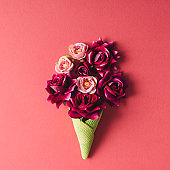 Purple flowers and green icecream cone on pink background.