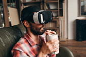 Man drinking cocktail while using vr glasses