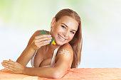 Beautiful girl using sunscreen