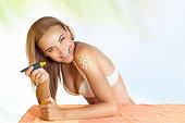 Happy woman applying sunscreen
