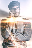 Double exposure of city and man using phone