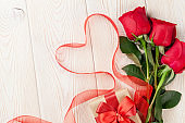 Red roses and heart shape ribbon over wood