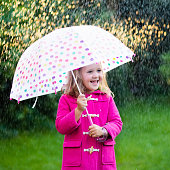 Little girl with umbrella in rainy summer park