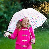 Little girl playing with umbrella in the rain