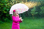 Laughing little girl with umbrella in the rain