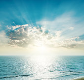 rising sun on the horizon, blue sea and clouds