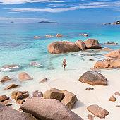 Woman enjoying Anse Lazio picture perfect beach on Praslin Island