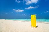 Sunscreen cream bottle on the beach