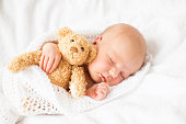 Newborn baby girl sleeping with teddy bear
