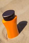 Plastic bottle of suncream  in the sand